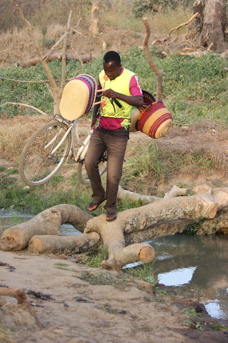 Baskets in one hand and a bicycle in the other