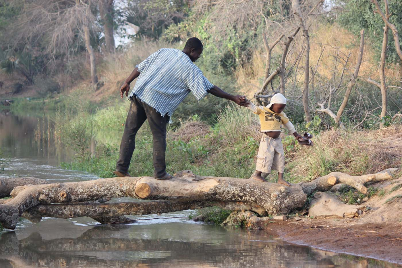 A father holding his child's hand as they cross the water