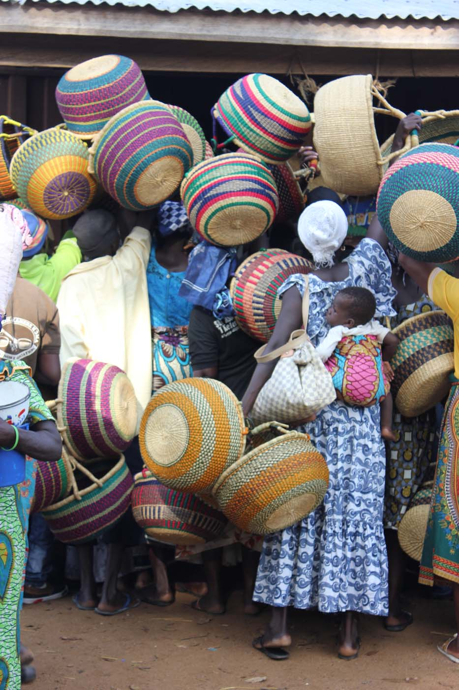 A throng of weavers and villagers offer up their baskets to sell